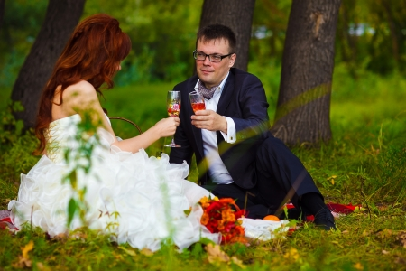 bride redhead and groom at wedding in green field sitting on picnic, drink wine from wine glasses photo