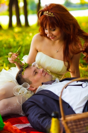 in Russia couple bride and groom communicate sitting on green grass, picnic in woods at wedding camping large portrait photo