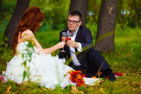 in Russia newlyweds couple bride and groom sitting on green grass, picnic in woods at wedding drink wine photo