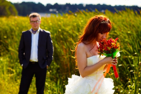 Red head Bride smelling wedding bouquet on background of green grass and groom photo