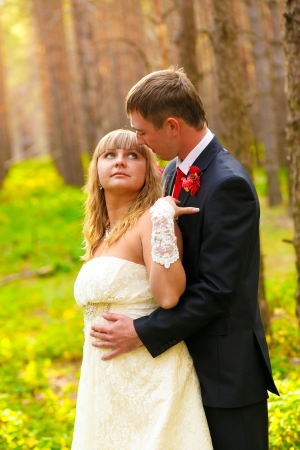 Bride and groom standing in a pine forest in autumn, the newlyweds a wedding, a man looks at a woman photo
