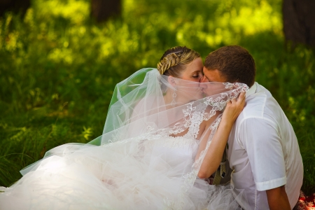 beautiful bride groom newlyweds standing in a green forest in summer at a wedding summer photo