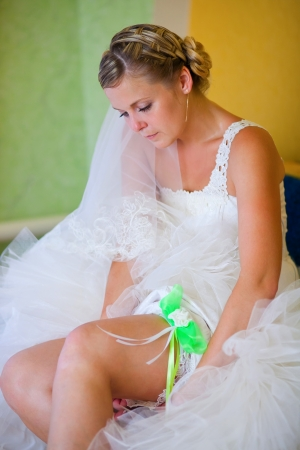 blonde bride at a wedding in the house wears a garter on the leg photo
