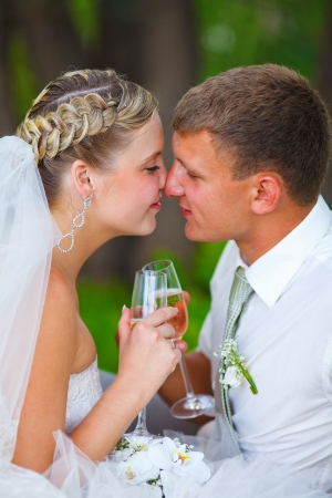 Bride and groom at wedding couple holding glass of touching and kissing each others noses. on a green background  photo