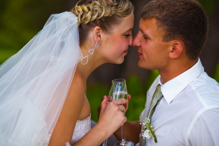 Bride and groom at wedding couple holding glass of touching and kissing each others noses on a green background photo