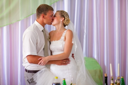 bride and groom kissing newlyweds room at a banquet in the hall of wedding day photo