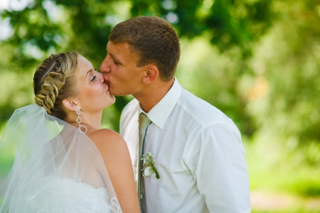 bride and groom newlyweds kissing in the woods on a green background Wedding Day photo