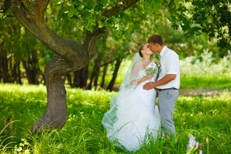 bride and groom newlyweds kissing in woods on green background Wedding Day
