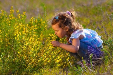 little baby girl is studying touching look at a yellow flower in a green field of grass in the spring on a sunny day photo