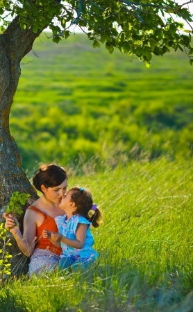 mother, daughter, woman and child sitting in the green grass near a tree in the photo tenderness and family