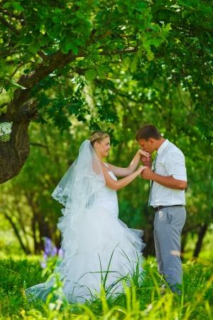 bride groom kissing hand of blonde bride, newlyweds couple are in a green forest in wedding summer photo