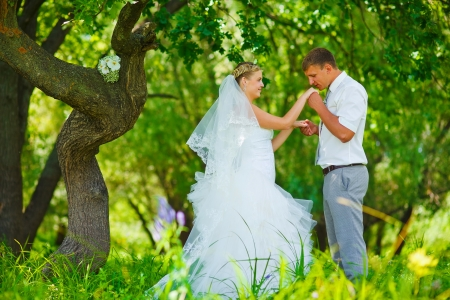 bride groom kissing hand of blonde bride, newlyweds couple are in green forest in wedding summer photo