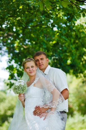 bride groom newlyweds blonde standing in a green forest in summer at a wedding photo