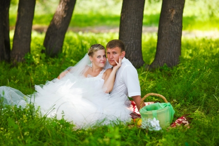 couple at wedding newlyweds a picnic in a forest glade, the bride groom holding his face photo