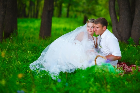 couple at wedding newlyweds a picnic in forest glade, bride groom holding his face photo