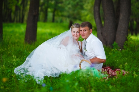 couple at wedding newlyweds picnic in a forest clearing, bride groom sitting in green forest photo