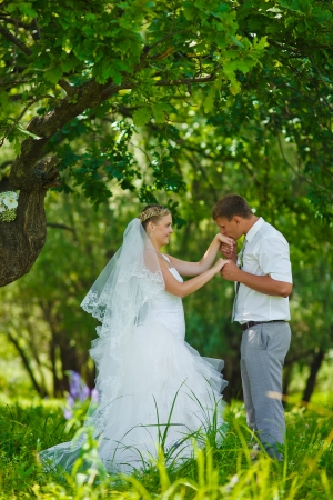 groom kissing hand of blonde bride, newlyweds couple are in a green forest in summer wedding photo