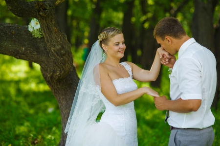 groom kissing hand of bride, newlyweds couple are in a green forest in summer wedding photo