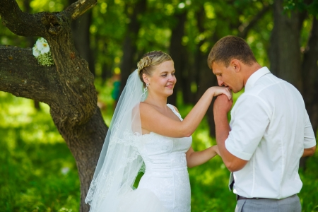 groom kissing hand of bride, newlyweds couple are in green forest in summer wedding photo