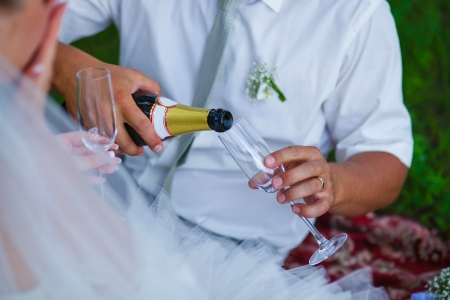 groom pours wine into a glass at wedding at picnic in a green forest in summer photo