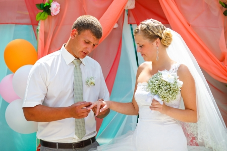 groom wears ring bride wedding couple are at time of registration photo
