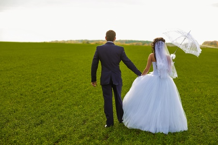 bride and groom outdoor standing in a green field hug, newlyweds with umbrella  in nature ass back view photo