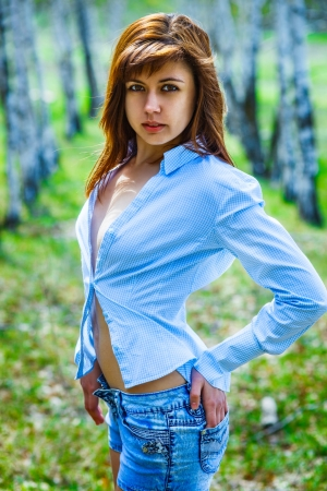 sexy brunette woman in a blue shirt and shorts on the nature of photo