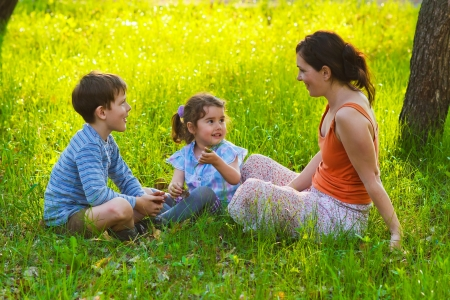 boy and girl woman mom son daughter children are sitting on