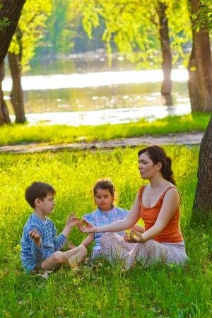 natur: figlia, madre e figlio seduti all'aperto picnic meditazione natur