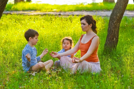 daughter mother and son sitting outdoors picnic meditation natur Stock Photo
