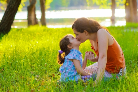 daughter mother kissing a baby woman sitting on the green grass