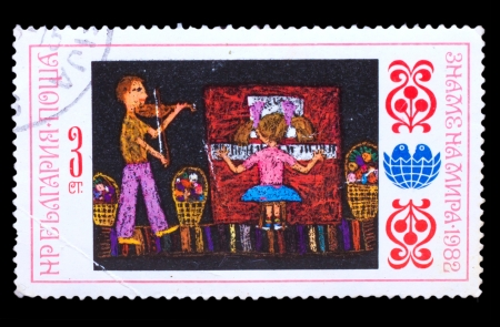 BULGARIA - CIRCA 1982: A stamp printed in BULGARIA, girl plays piano and boy playing violin, circa 1982 photo