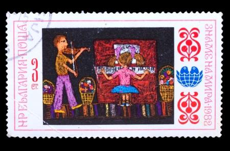 bulgaria girl: BULGARIA - CIRCA 1982: A stamp printed in BULGARIA, girl plays piano and boy playing violin, circa 1982