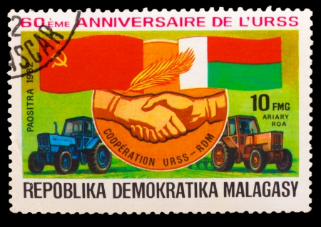 soviet flag: MALAGASY - CIRCA 1982: A stamp printed in MALAGASY, Democratic Republic of Malagasy, Soviet flag and Malagasy, handshake hand, tractor Belarus, circa 1982