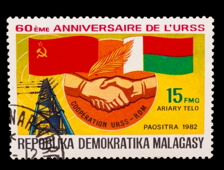 soviet flag: MALAGASY - CIRCA 1982: A stamp printed in MALAGASY, Democratic Republic of Malagasy, Soviet flag and Malagasy, handshake hand, radio tower station, circa 1982 Stock Photo