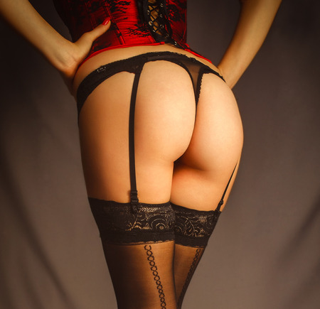 Sexy woman girl ass in close-up lingerie stockings with suspenders and red corset erotic sex photo