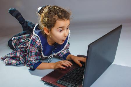 girl looking surprised and netbook isolated on photo