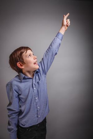 raised: on gray background boy raised his hand up