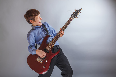 Teen boy playing guitar on gray background
