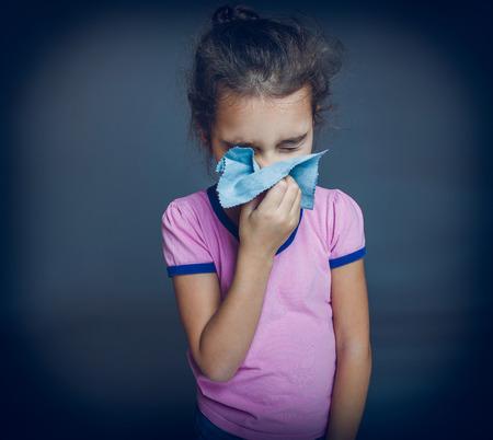 cros: teen girl is sick sneezes handkerchief on a gray background cros