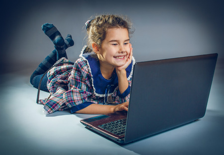 cross process: teen girl playing laptop on gray background cross process
