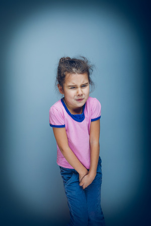 urination: Teen girl wants to use the toilet on a gray background cross pro
