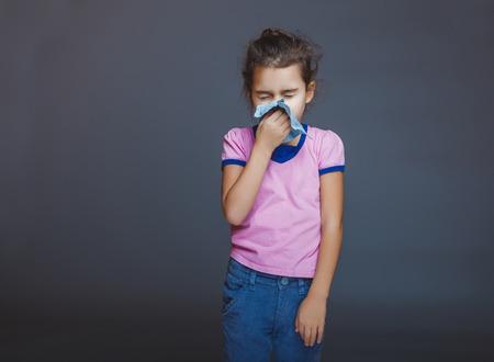Teenage girl suffers a handkerchief on gray background