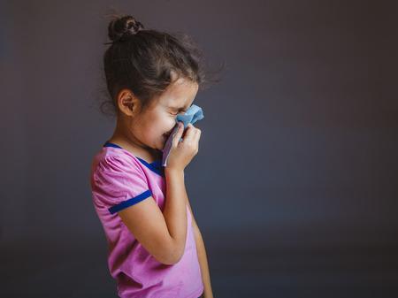 Teenage girl suffers runny nose handkerchief on a gray backgroun