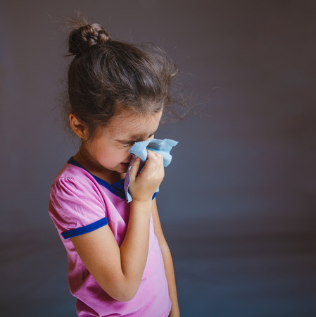 Teenage girl suffers runny nose sneezing handkerchief on a gray