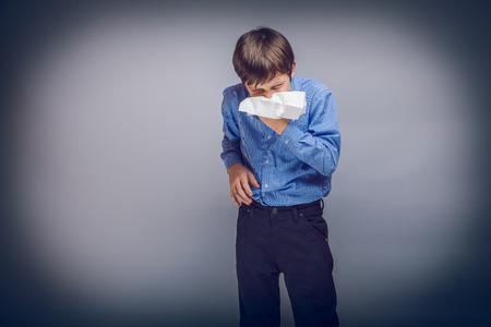hombres jovenes: muchacho adolescente que sopla su pelo de la nariz marr�n de aspecto europeo