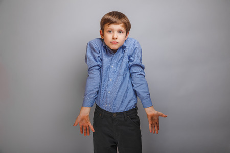 shrugs: teenager boy in a shirt shrugs