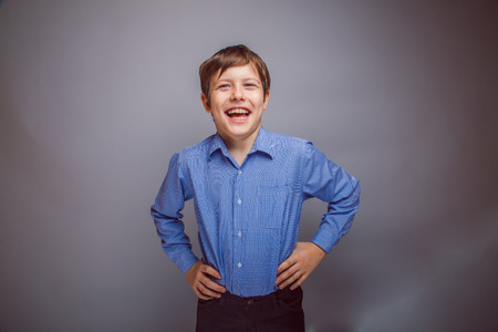 rejoices: teenager boy rejoices over gray background