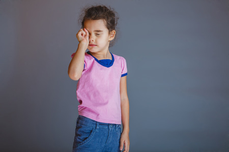 the girl  child  is tired rubs his eyes on gray background photo