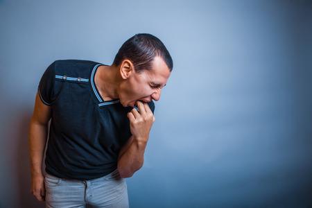 oorzaken: de man van de Europese uitstraling donkerbruin ziek oorzaken braken putti
